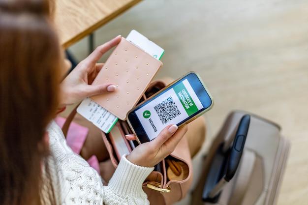 Frau von oben, die ausweisdokumente impfbescheinigung auf smartphone-bildschirm am flughafen hält