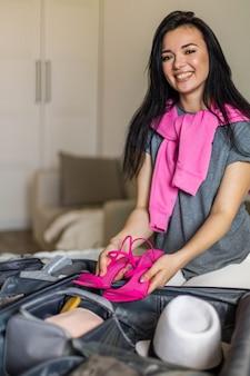 Frau von oben, die eleganz rosa sandalen in den koffer setzt, der bereit ist, sommerurlaub zu machen?