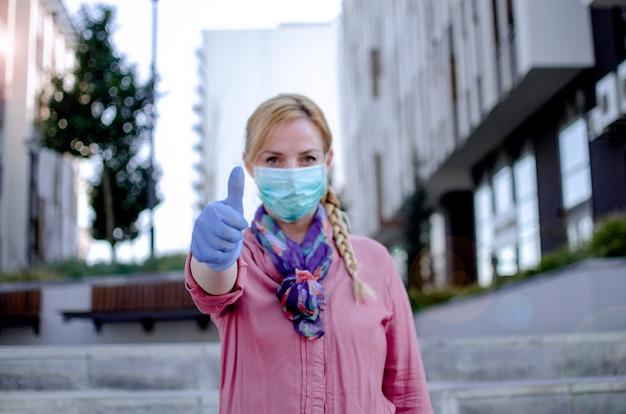Frau vor dem krankenhaus zeigt daumen hoch glücklich für covid-19-test ist negativ. tests auf ansteckende krankheiten pünktlich geben gute ergebnisse. sie wird in ordnung sein