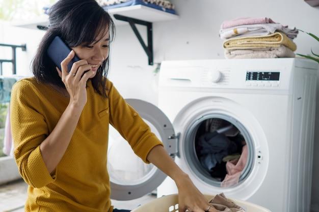 Frau vor der waschmaschine, die einige wäsche macht, die kleidung innen während des telefonanrufs lädt