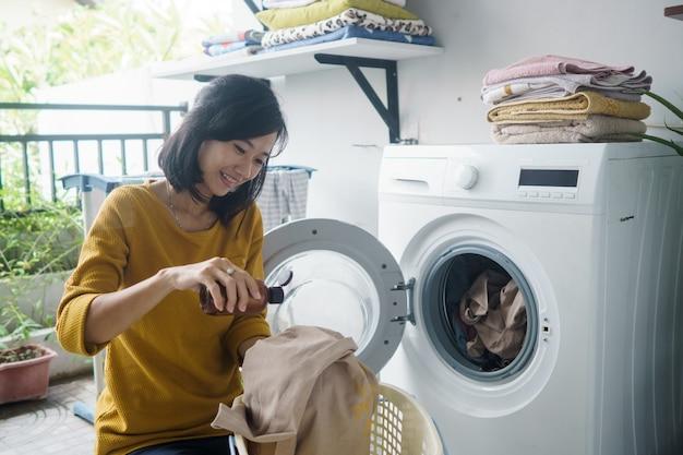 Frau vor der waschmaschine, die einige wäsche macht, die kleidung nach innen lädt