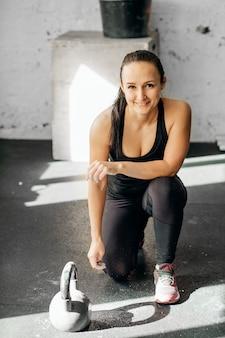 Frau vor einem schweren kettlebell-training in einem fitnessstudio