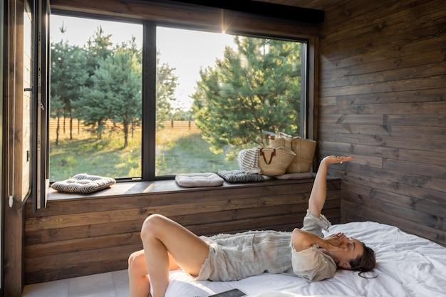 Frau wacht in einem landhaus oder hotel mit panoramafenstern im kiefernwald auf und hob gähnend die hände. guten morgen und erholung zum naturkonzept