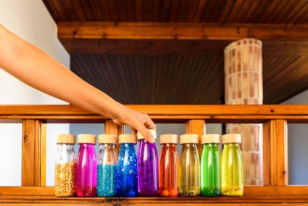 Frau wählt eine flasche ruhe unter allen hellen farben, um sich zu entspannen.