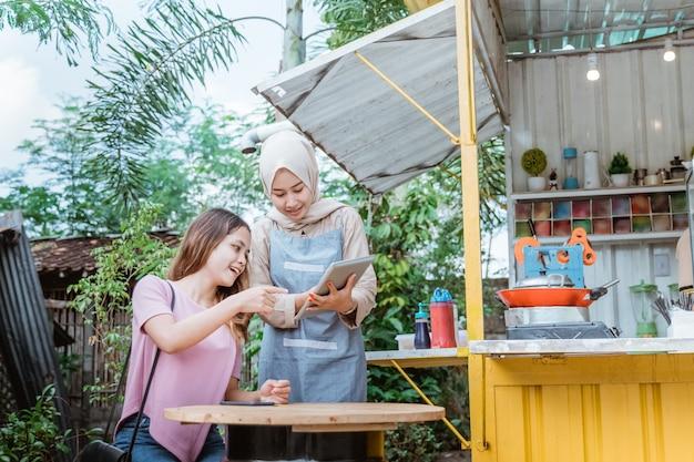 Frau wählt essen ein menü, das ein verkäufer an einem kleinen essensstand bringt
