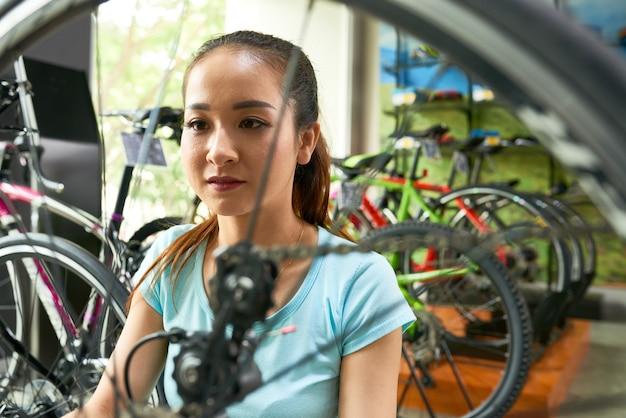 Frau wählt fahrrad im laden