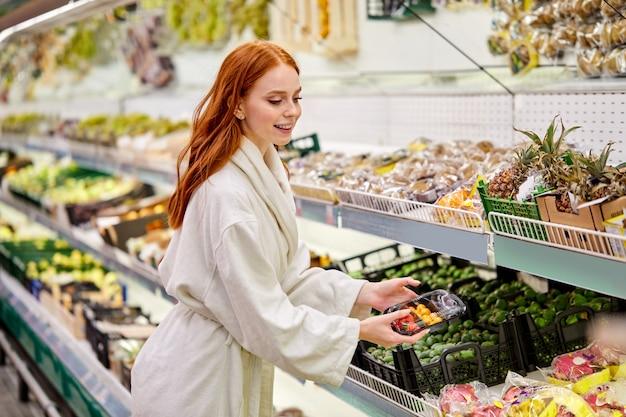 Frau wählt frisches gemüse und obst im laden, trägt bademantel. junge frau, die lebensmittel im supermarkt kauft