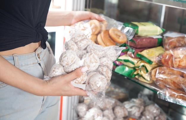 Frau wählt gebäck im supermarkt.