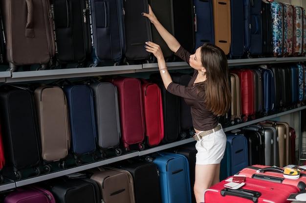 Frau wählt großen koffer am shop