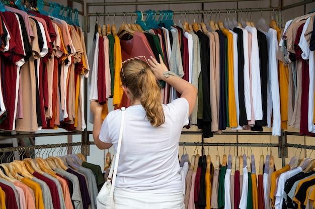 Frau wählt kleidung durch den sender im laden auf dem markt. rückansicht
