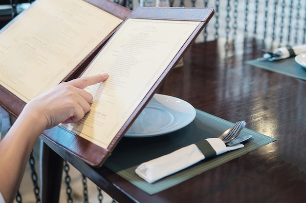 Frau wählt lebensmittel in einem menü, um im restaurant zu bestellen