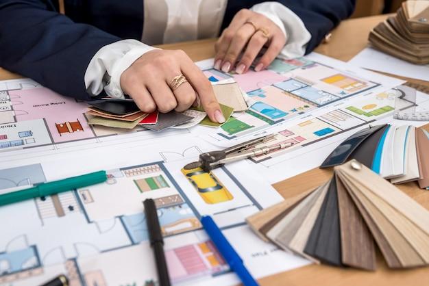 Frau wählt materialien mit farbpalette für hauptprojekt