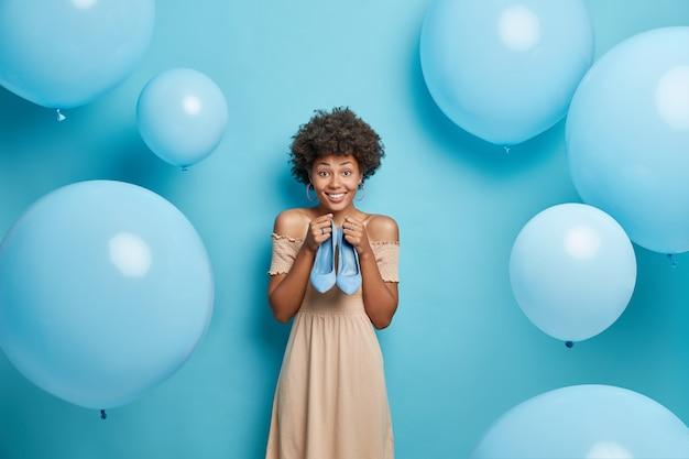 Frau wählt outfit für date trägt braunes cocktailkleid hält blaue hochhackige schuhe bereitet sich auf partyposen vor