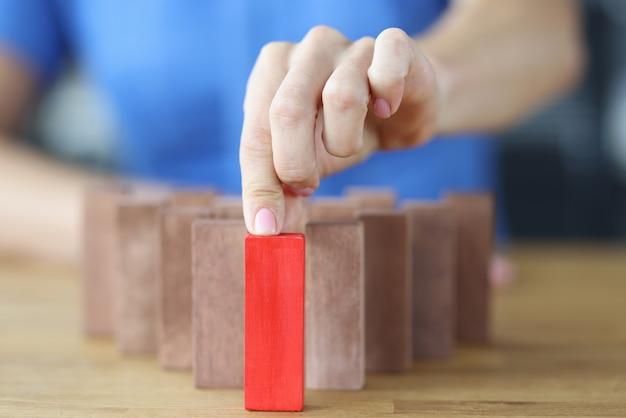 Frau wählt roten holzblock unter anderem auf holztisch und trifft richtiges entscheidungskonzept