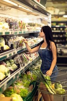 Frau wählt salate im laden käufer wählt gesundes essen