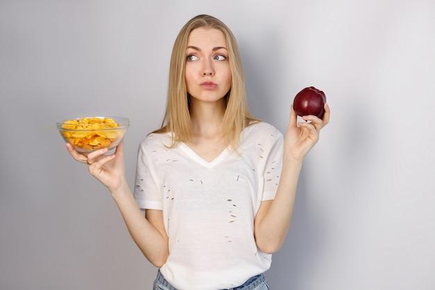 Frau wählt zwischen chips und rotem apfel auf grau abgewinkeltem hintergrund