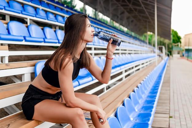 Frau während der pause zwischen sporttraining auf dem stadion, das auf einer bank sitzt