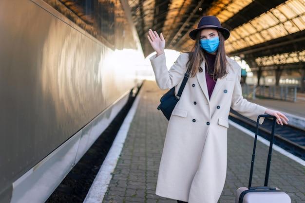 Frau während einer pandemie am leeren bahnhof