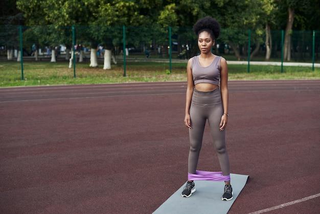 Frau während ihres fitness-trainings im freien mit gummi-widerstandsband.