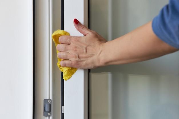 Frau wäscht eine offene tür zum balkon mit einem gelben lappen