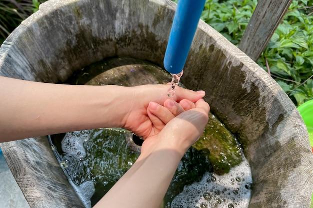 Frau wäscht ihre hände mit wasser im freien an einem öffentlichen wasserhahn