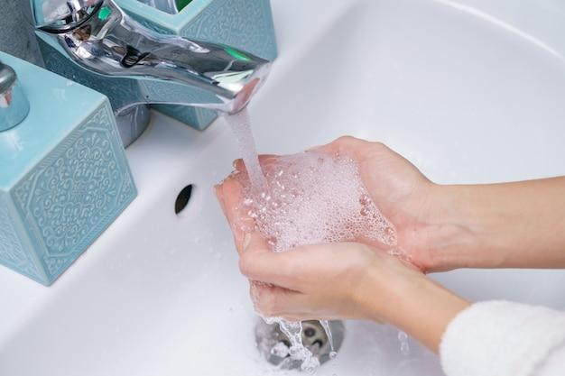 Frau wäscht ihre hand im waschbecken