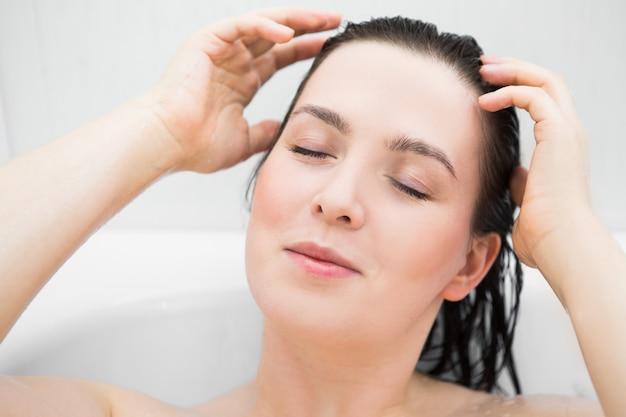 Frau wäscht sich im badezimmer den kopf