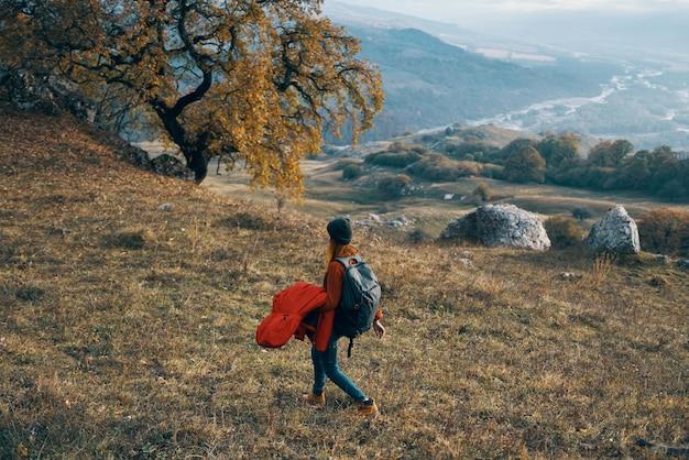 Frau wanderer in herbstkleidung neben einem hund geht auf naturbergen