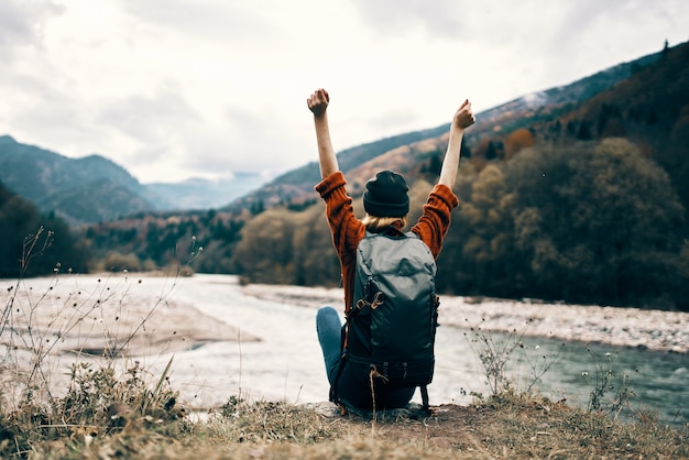 Frau wanderer mit rucksack in der nähe von flussbergen landschaftsfreiheit