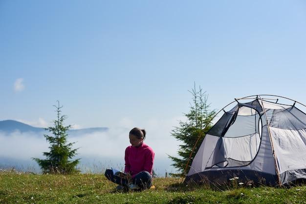Frau wanderer sitzt auf grünem gras des blühenden tals am touristenzelt unter schönem blauem himmel, der ein buch am hellen sommermorgen liest