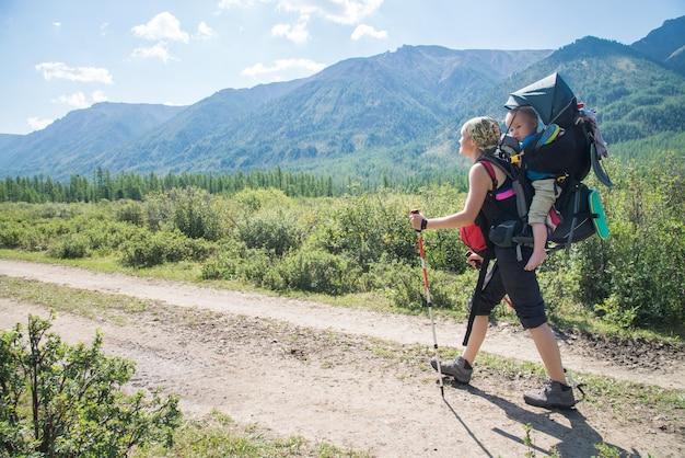 Frau wanderer trekking in den bergen mit kind im rucksack