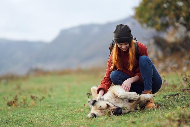 Frau wandererin mit einem rucksack auf natur in den bergen wird mit einer hundefreundschaft gespielt