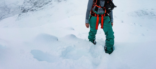 Frau wandert auf einem verschneiten berg hiking
