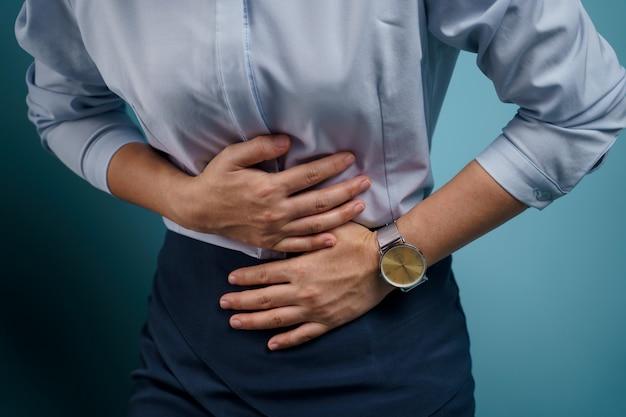 Frau war krank mit bauchschmerzen händchen haltend drückte ihren bauch.