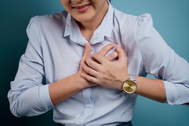 Frau war krank mit brustschmerzen auf blau isoliert.