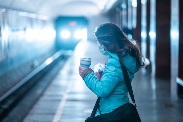 Frau warten an einer u-bahnstation in kiew.