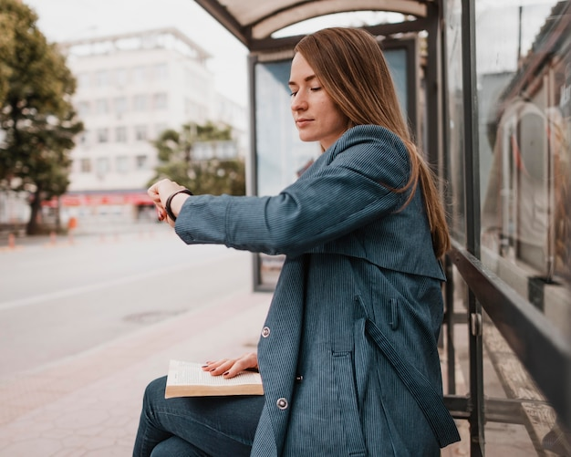 Frau wartet auf den bus und sitzt mit einem buch auf ihrem schoß