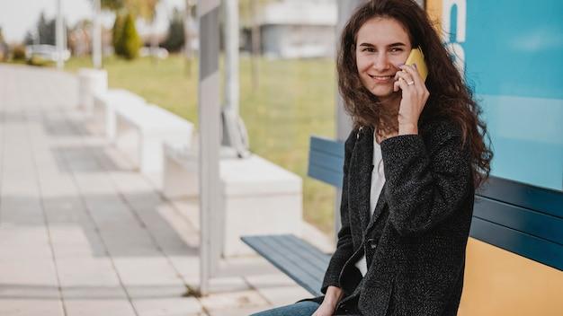 Frau wartet auf den bus und spricht am telefon