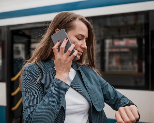 Frau wartet auf den bus und überprüft die zeit