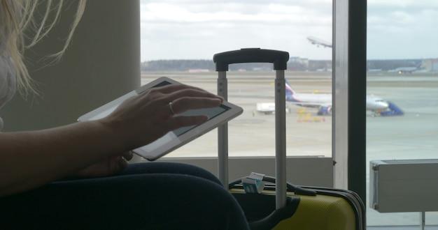 Frau wartet auf den flug mit tablet-pc