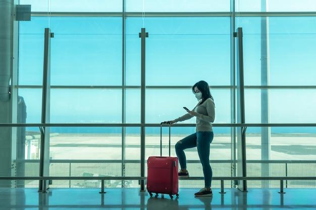 Frau wartet auf flugzeug am flughafenterminal mit smartphone - fuerteventura - spanien
