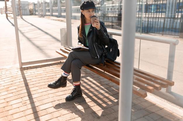 Frau wartet in der straßenbahnhaltestelle
