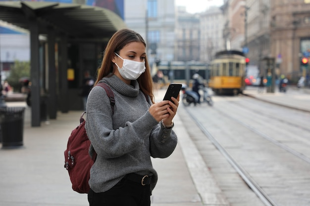 Frau wartet straßenbahn mit schützender gesichtsmaske, die ticket online mit smartphone kauft