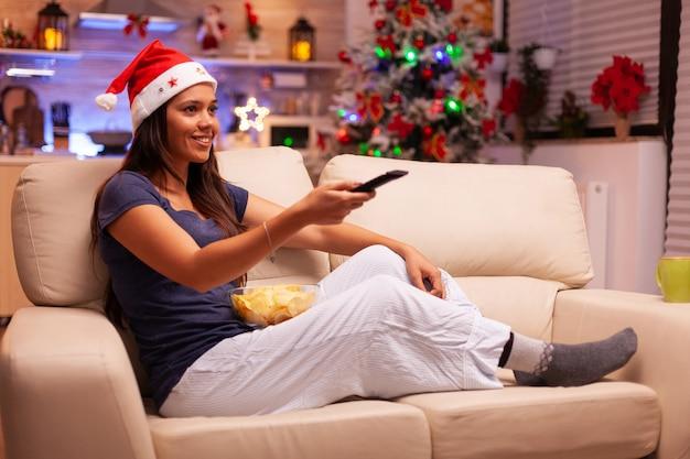 Frau wechselt den kanal mit fernbedienung und sieht lustige weihnachtskomödien an