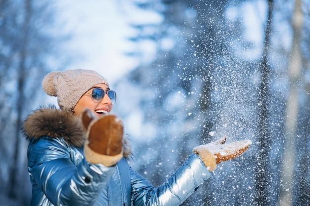 Frau weht schnee von handschuhen