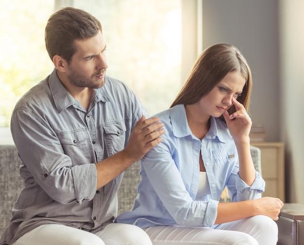 Frau weint, während ehemann sie beruhigt.