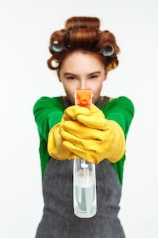 Frau weist auf spray mit gelben handschuhen auf händen