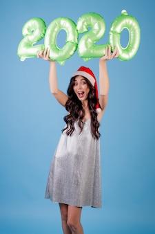 Frau, welche die 2020 ballone des neuen jahres tragen weihnachtshut und -kleid hält