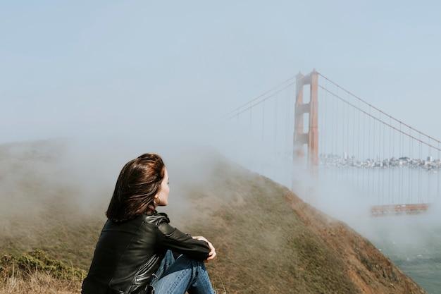 Frau, welche die ansicht der golden gate bridge in san francisco genießt