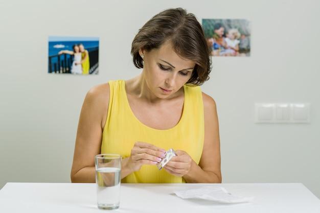 Frau, welche die anweisungen, ein paket der pillen anhalten betrachtet